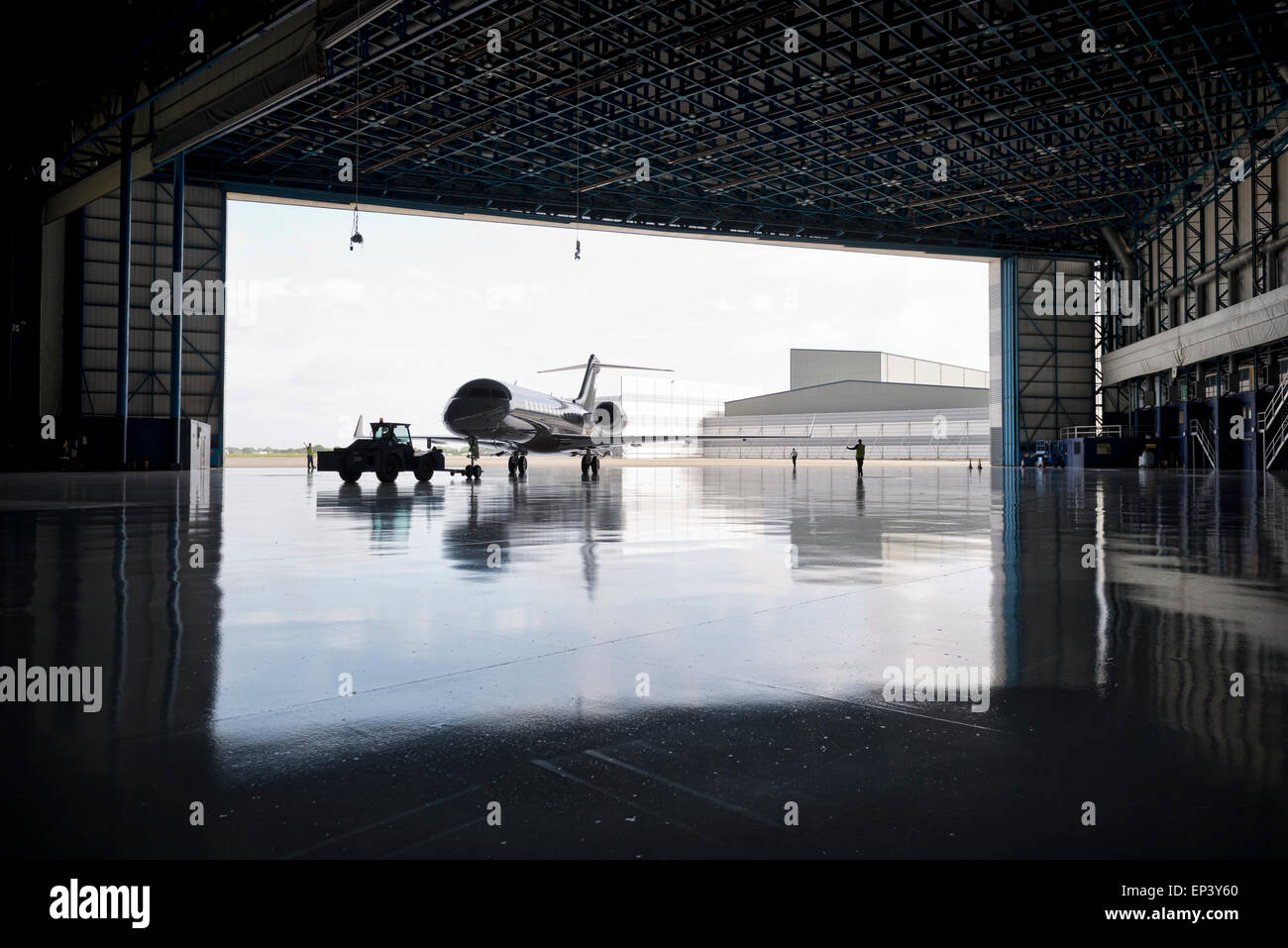 Aircraft being maneuvered on the ground into a hanger - Stock Image