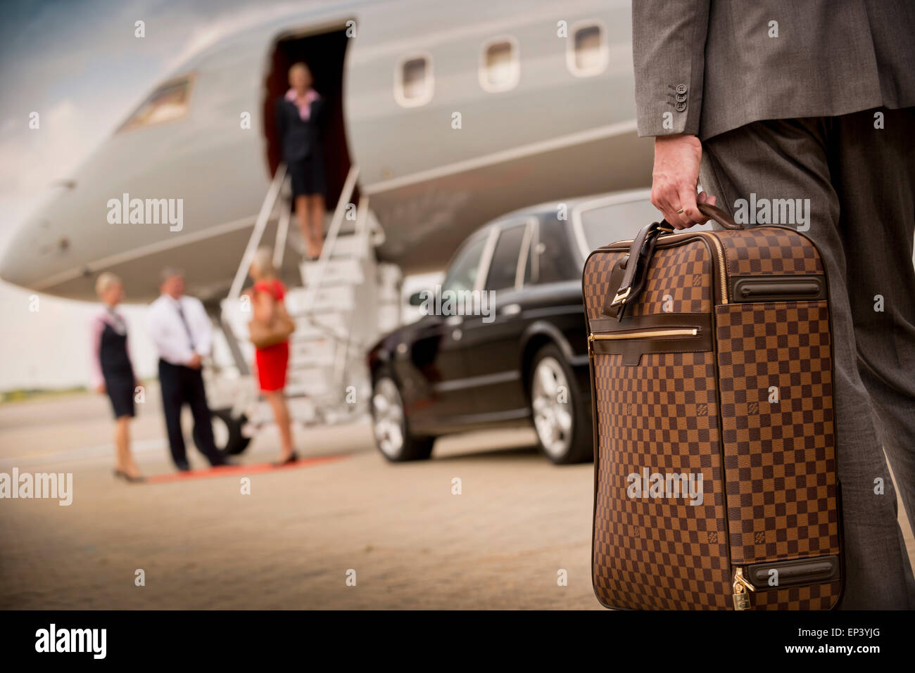 Suitcase being carried to a private airplane as passenger embarks flight - Stock Image