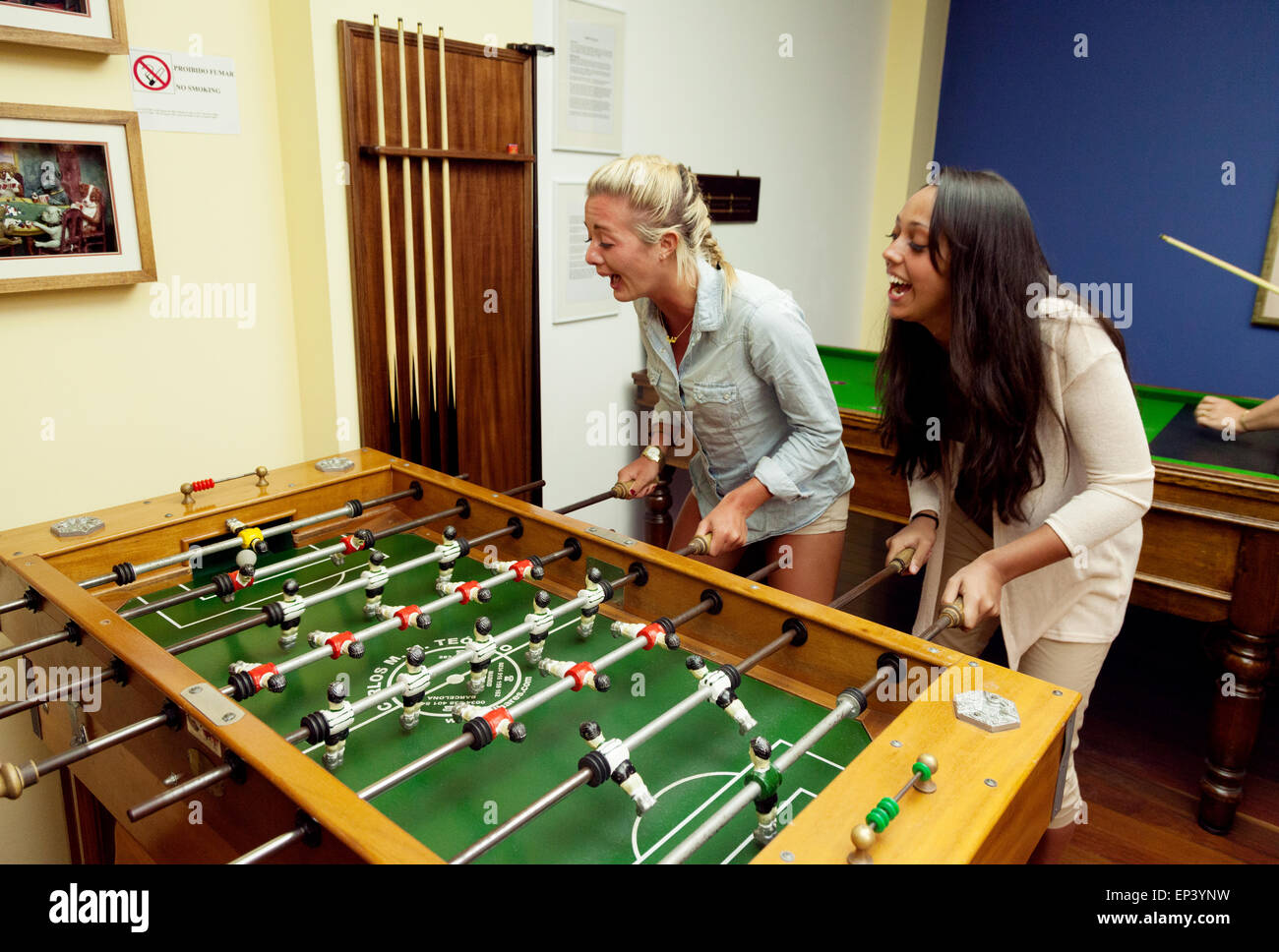 Two women playing table football in a bar, Madeira, Europe - Stock Image