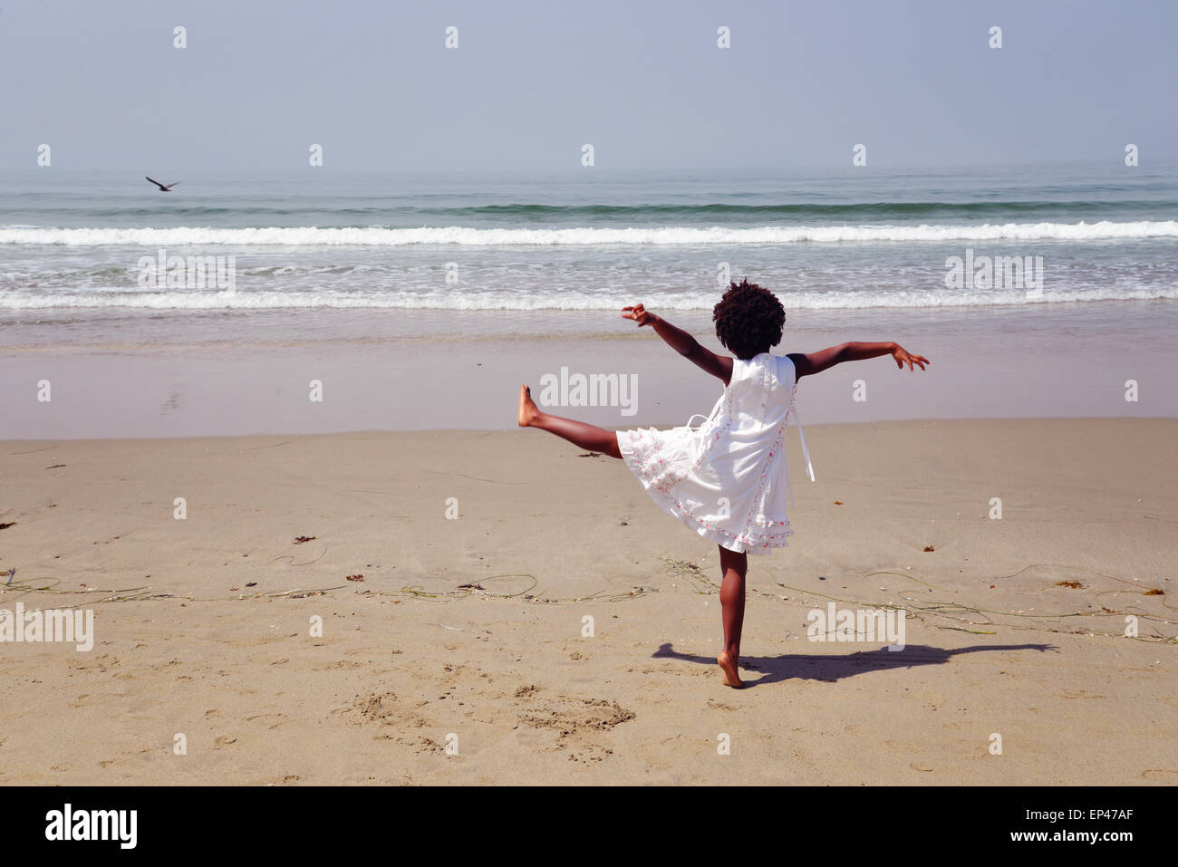 Rear view of an african american girl standing on one leg on the beach - Stock Image