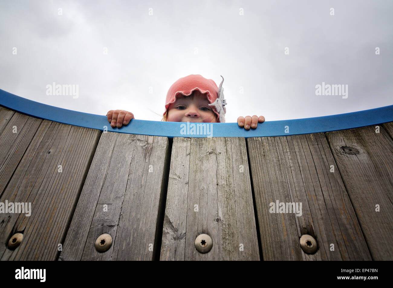 Girl looking down over the edge of a wooden climbing frame - Stock Image