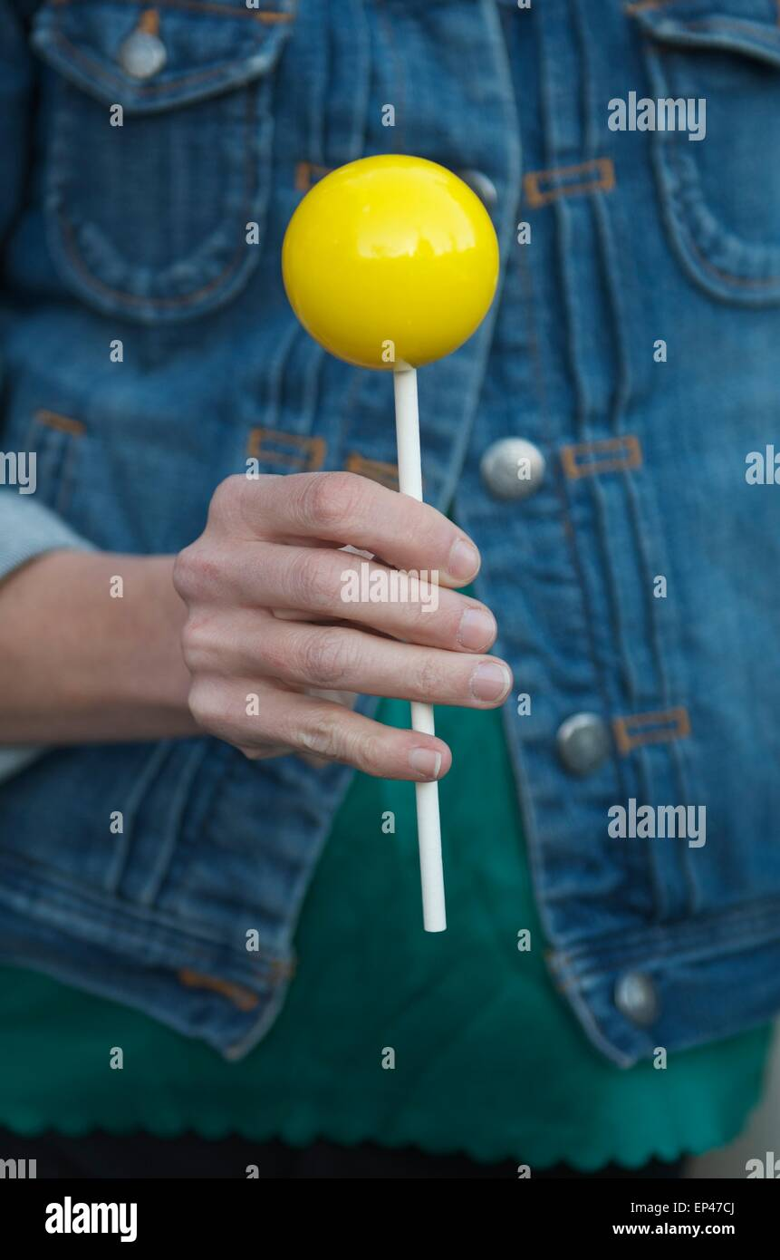 Close up of a woman holding a big yellow lollipop - Stock Image