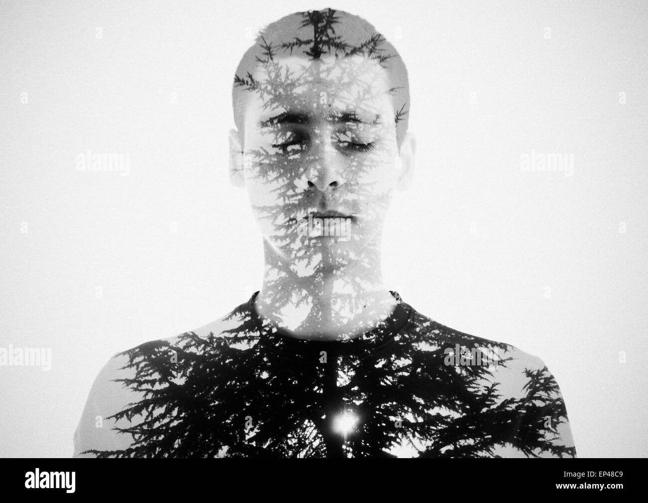 Double exposure portrait of a young man and a tree - Stock Image
