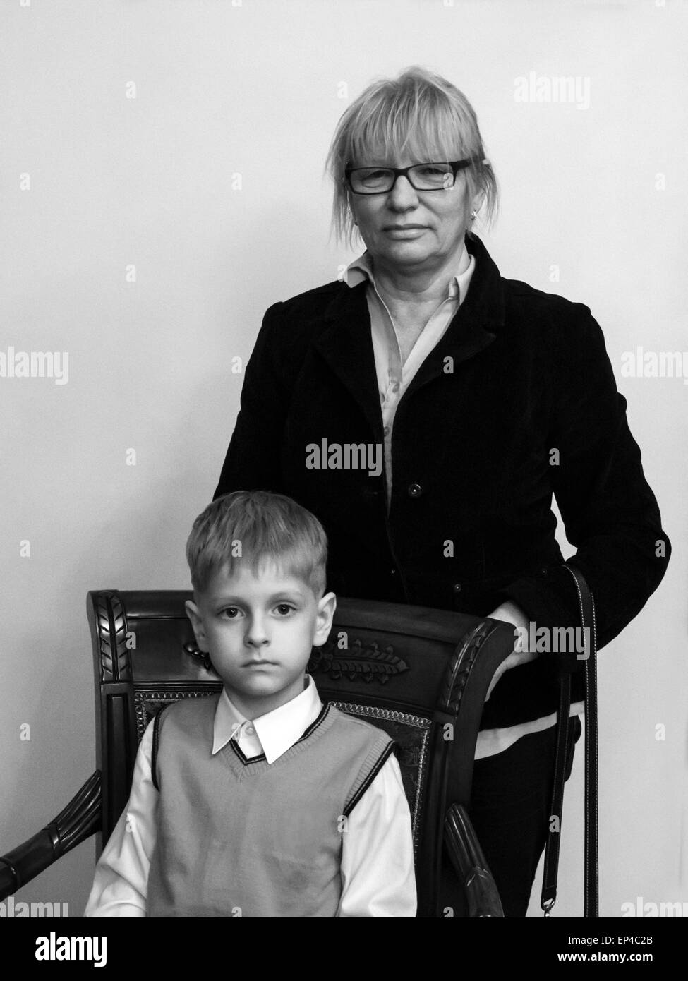 May 13, 2015 - Studio portrait of a grandmother and a grandson, a schoolboy sitting in a luxurious armchair (Credit - Stock Image