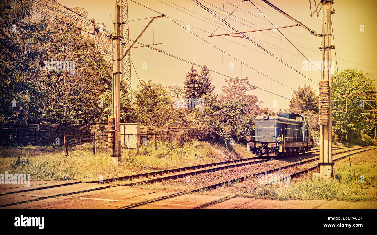 Retro toned picture of a locomotive on railway crossing, old film style. - Stock Image