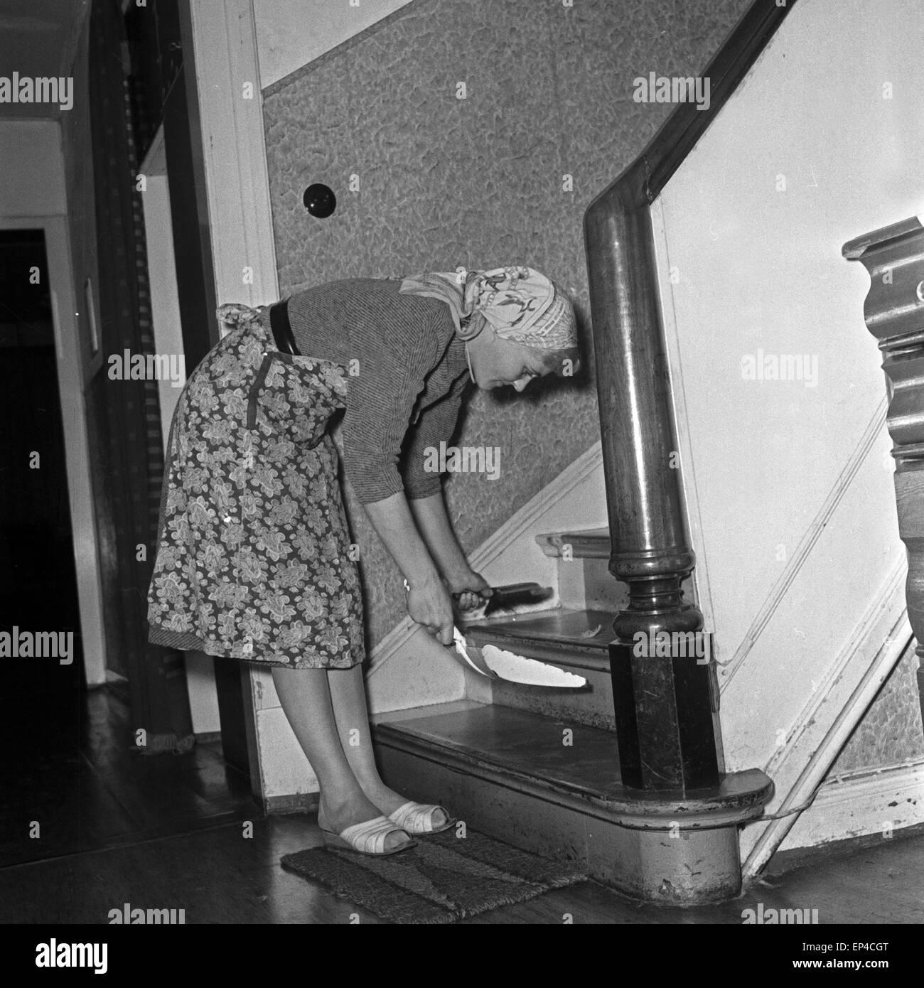 Eine Hausfrau kehrt das Treppenhaus, Deutschland 1950er Jahre. A housewife  is sweeping the staircase