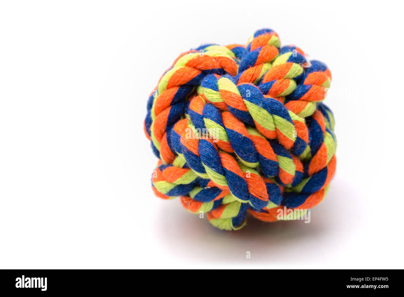 A very colorful ball made from rope tied in a monkey's fist knot used for a dog's toy. - Stock Image
