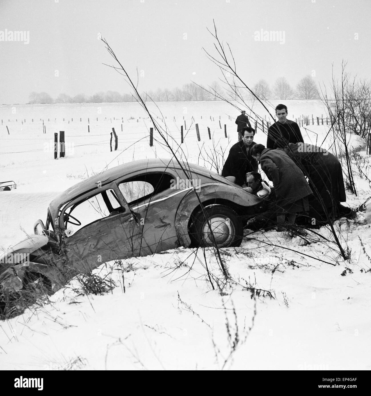 Ein VW Käfer ist bei einem Verkehrsunfall bei Schnee in den Straßengraben gerutscht, Deutschland 1960er - Stock Image