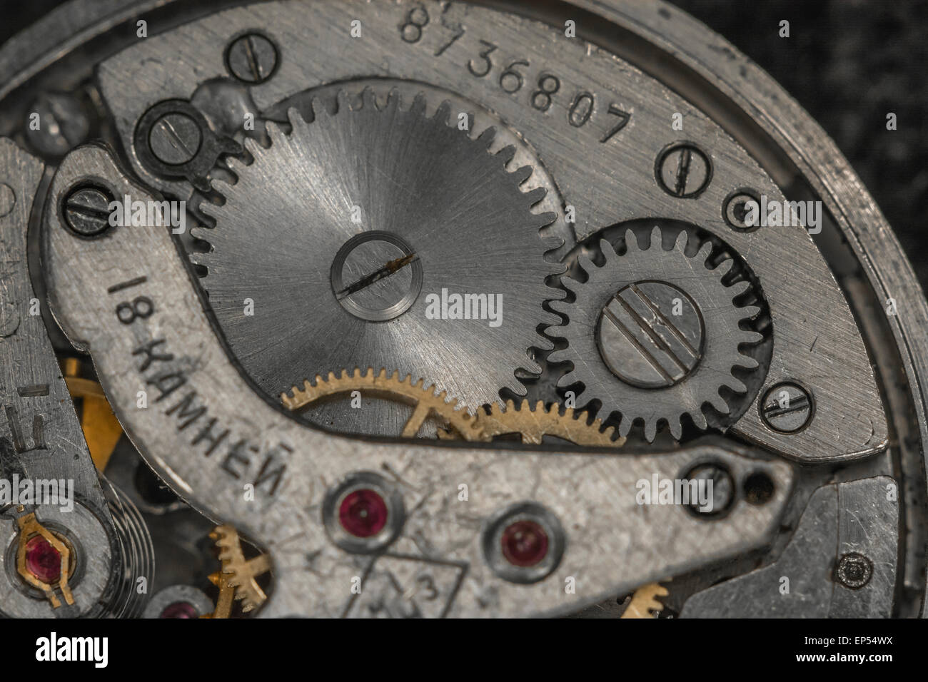 Macro-photo of Russian wristwatch mechanism. Key focus around centres of steel cogs in middle of picture. - Stock Image