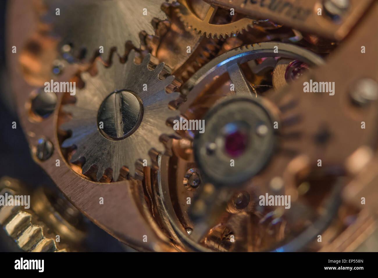 Macro-photo of wristwatch mechanism. Key focus on upper right hand teeth of steel cog to left half of picture. - Stock Image
