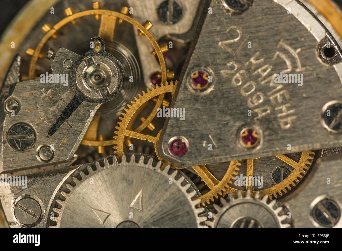 Macro-photo of Russian wristwatch mechanism. Key focus on teeth of brass cog in picture centre. - Stock Image