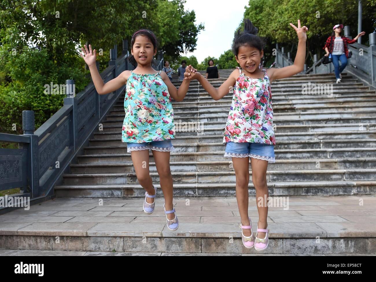 (150514) -- MOJIANG, May 14, 2015 (Xinhua) -- Twin sisters Jin Meixian (R) and Jin Huixian play at a park in Mojiang - Stock Image