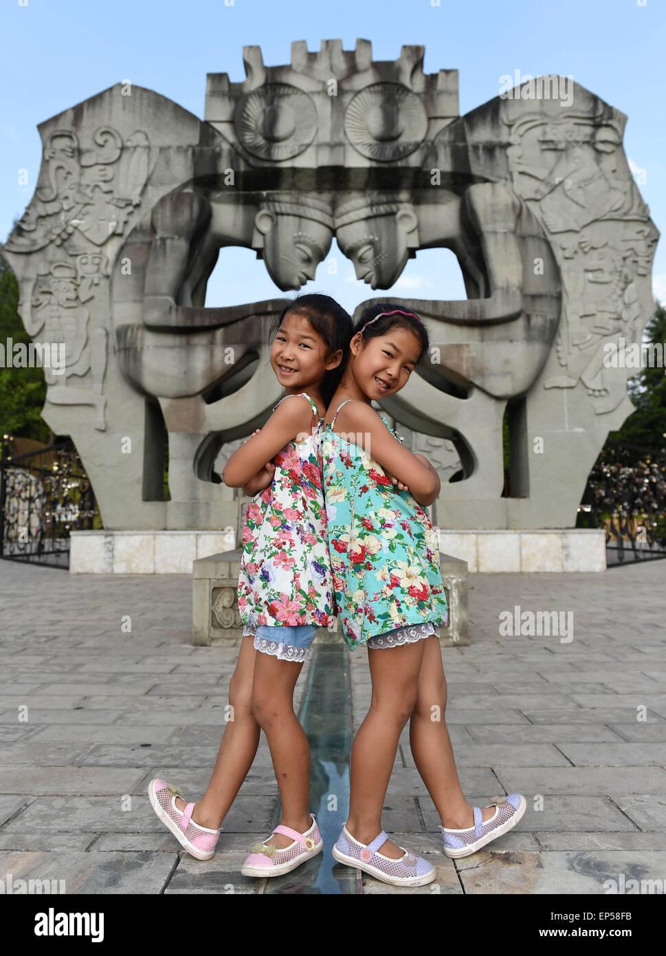 (150514) -- MOJIANG, May 14, 2015 (Xinhua) -- Twin sisters Jin Meixian (L) and Jin Huixian play at a park in Mojiang - Stock Image
