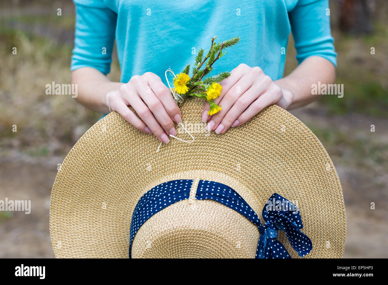 Straw hat and spring bouquet in hands of girl - Stock Image