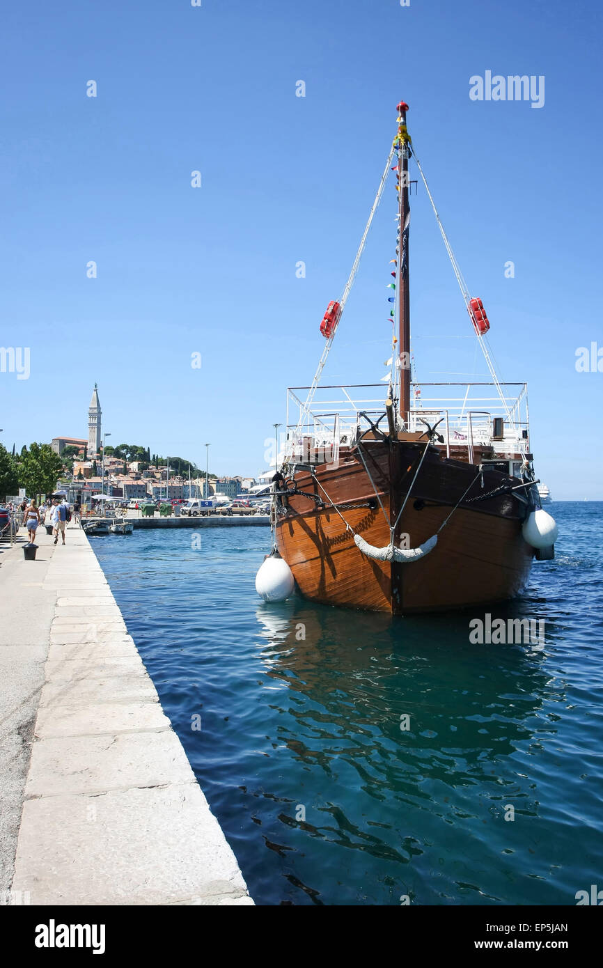 A galley anchored next to the dock with people walking on the seafront with the old city core in the background. - Stock Image