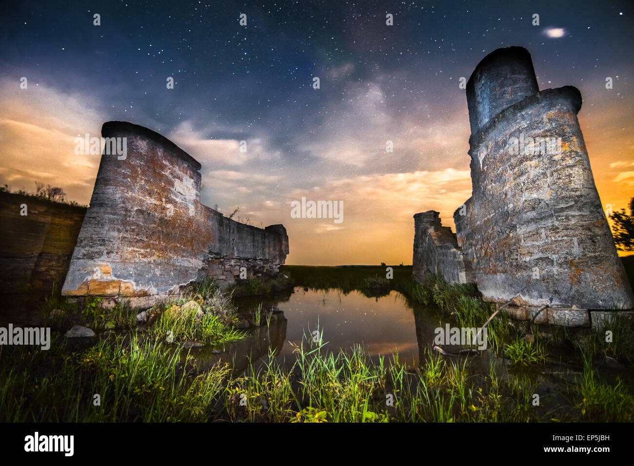 Old night castle wall ruins on lake reflections with stars sky - Stock Image