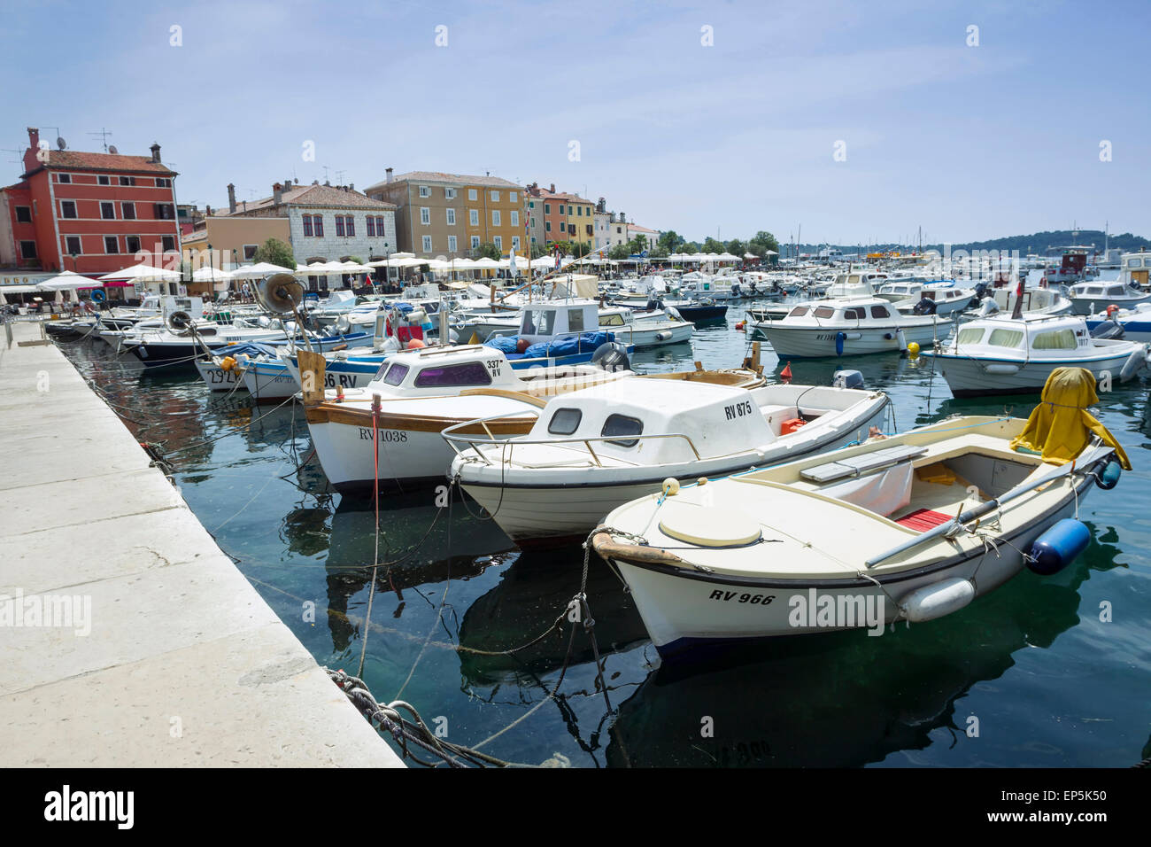 A large group of boats anchored in the marina with a view of the city promenade in Rovinj, Croatia. - Stock Image