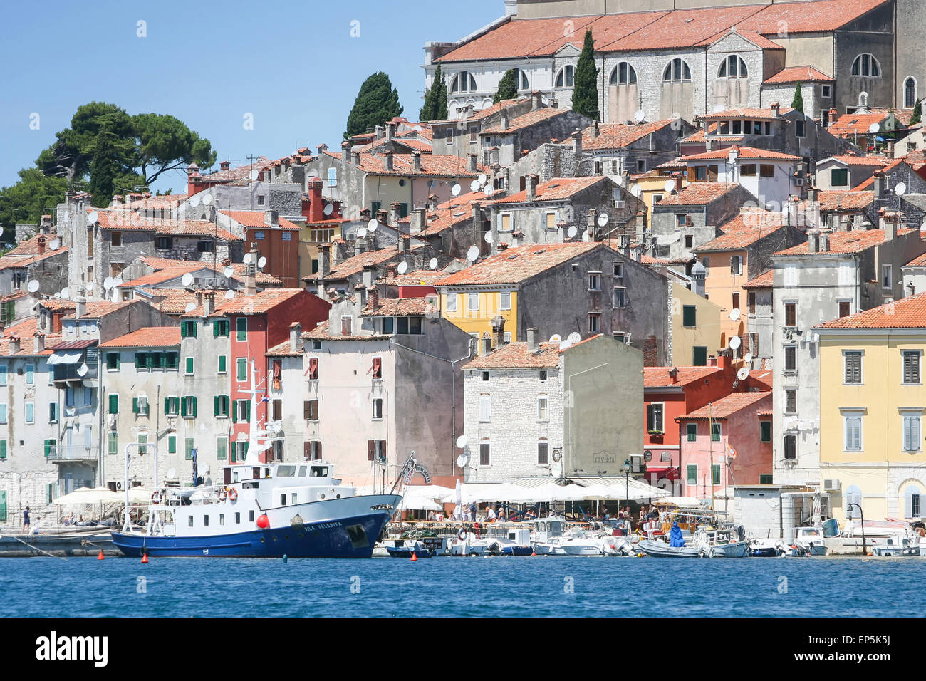 Old stone residential buildings of the old city core with boats anchored next to the seafront in Rovinj, Croatia. - Stock Image