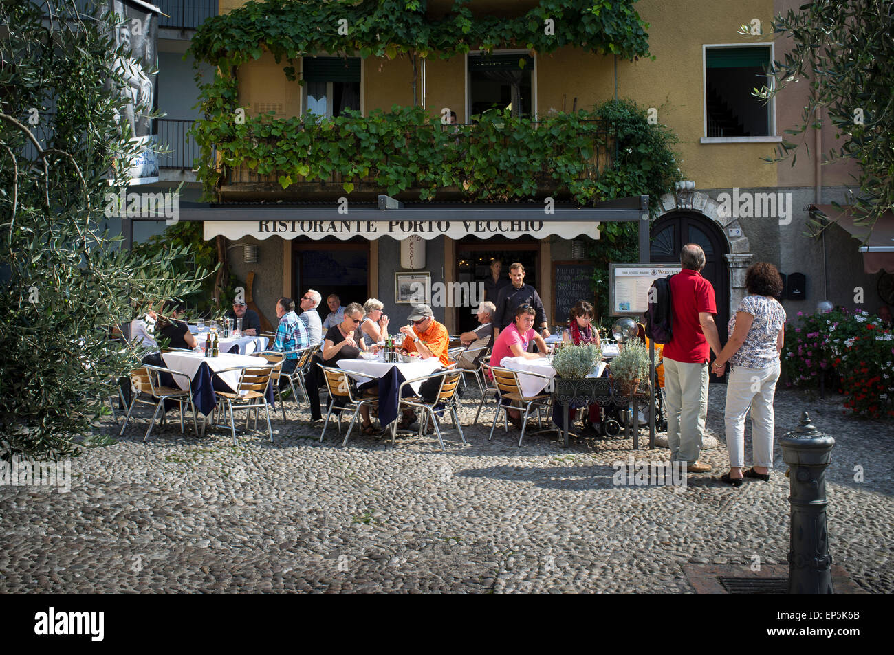 People enjoying dining al fresco outside a small restuarant in Malcesine, Lake Garda, Italy. - Stock Image