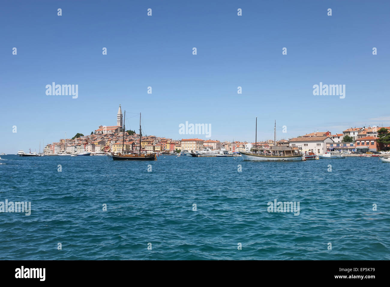 Ships anchored in the Adriatic sea and the old city core with the Saint Euphemia church in the background in Rovinj, - Stock Image