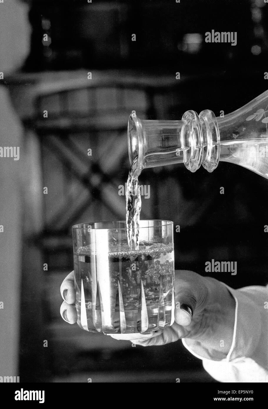 Eine Frau schenkt ein Glas Wasser ein, Deutschland 1980er Jahr. A woman puring a glass of water, Germany 1980s. - Stock Image