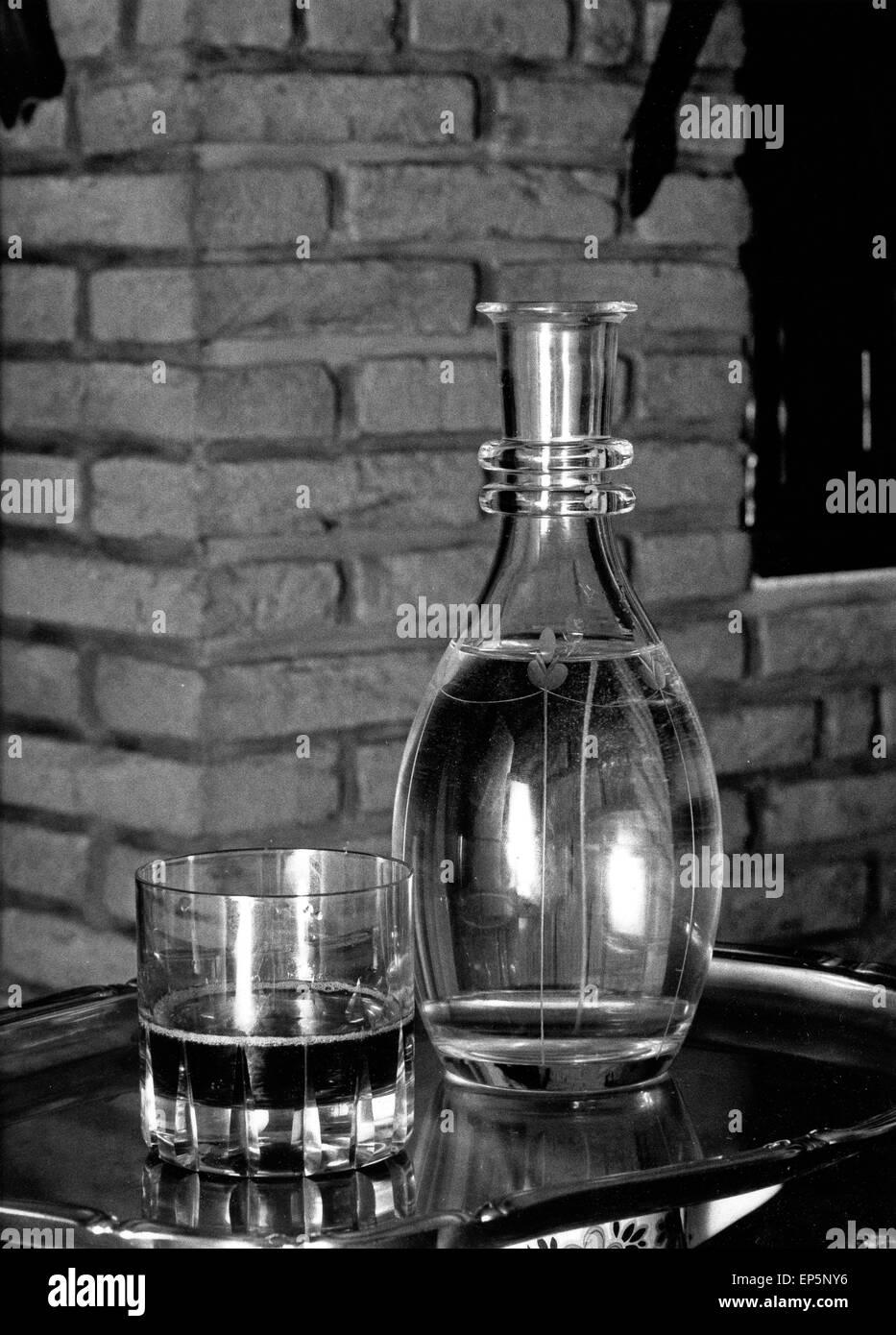 Eine Karaffe und ein gefülltes Glas daneben, Deutschland 1980er Jahre. A carafe and a half filled glass beside, - Stock Image