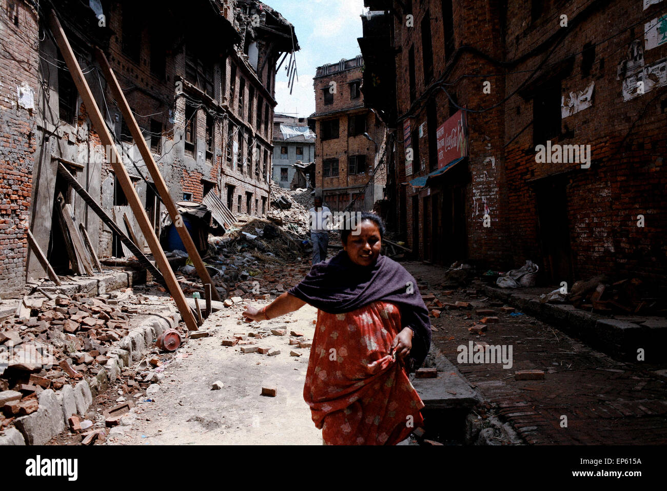 Nepalese woman runs past the damaged building in Bhaktapur on the outskirt Kathmandu. A massive earthquake of magnitude - Stock Image