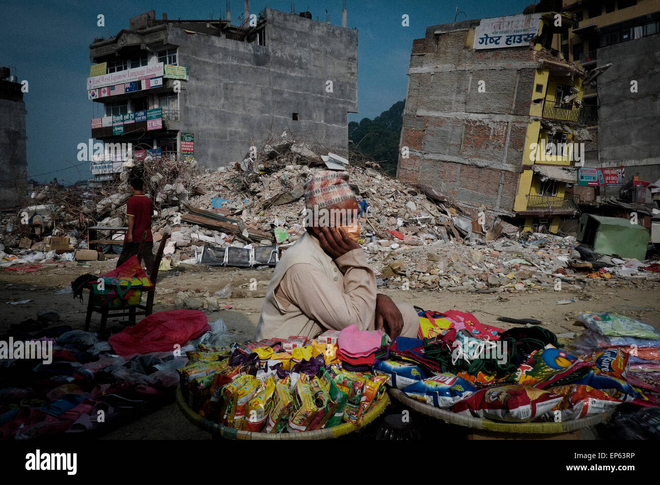 Nepalese starts their daily business in front of the damaged building. A massive earthquake of magnitude 7.4 hit - Stock Image