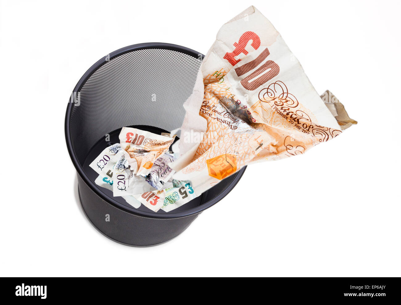Image of £10 note screwed up being thrown away in a wastepaper bin on white to illustrate wasting pounds GBP - Stock Image