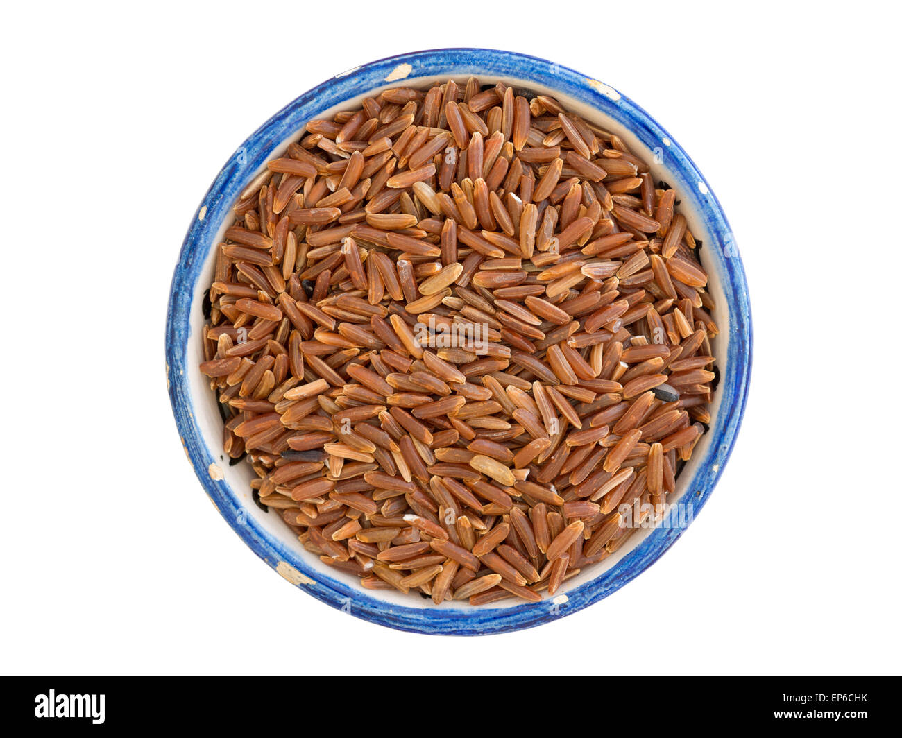 many dry ruby rice corns in small blue cup isolated on white - Stock Image