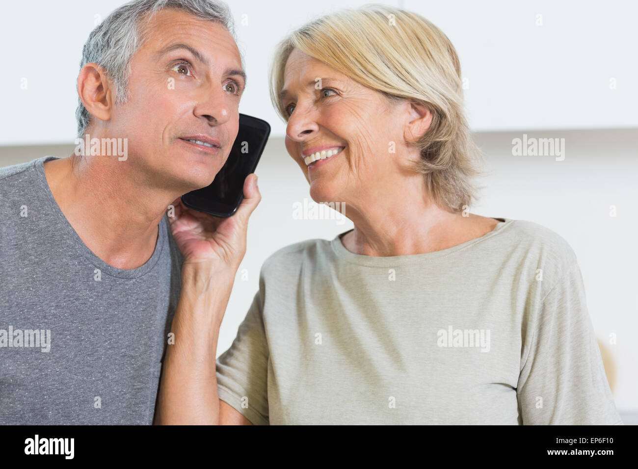 Happy mature couple listening a call together - Stock Image