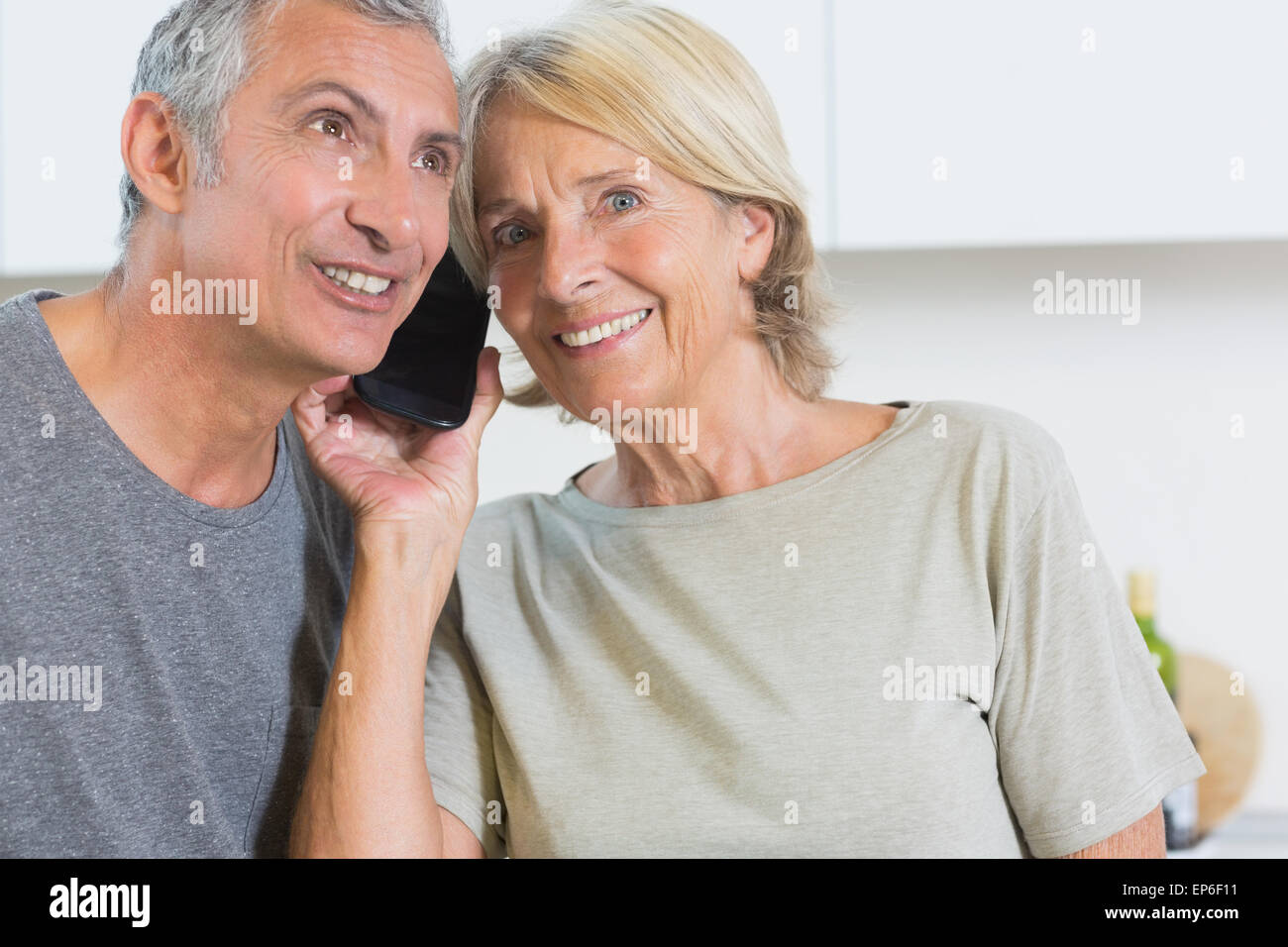 Cheerful mature couple listening a call together - Stock Image
