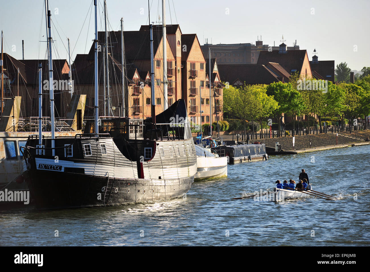 Rowers in a rowing boat pass a large sailing boat in the Bristol Harbour waters. - Stock Image