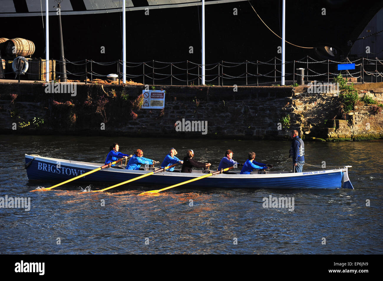 A rowing boat passes the SS Great Britain in the waters of Bristol Harbour. - Stock Image