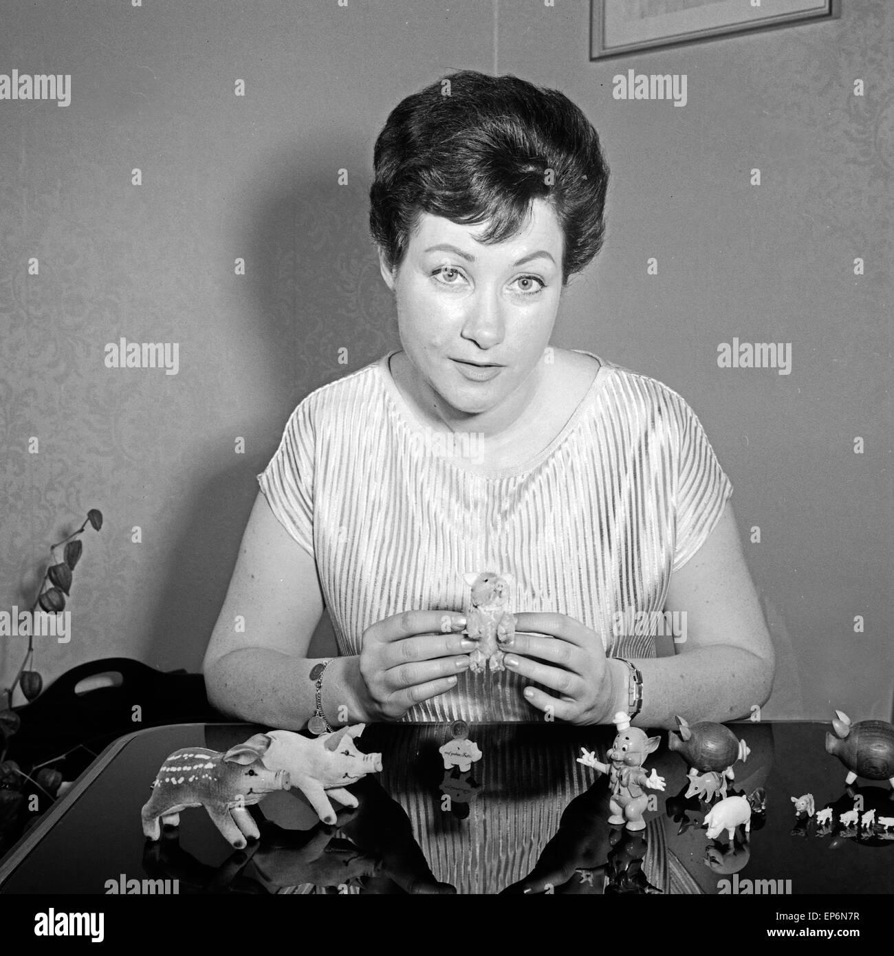 Österreichische Opernsängerin Melitta Muszely mit ihrer Sammlung von Schweinefiguren in Hamburg, Deutschland 1960er Stock Photo