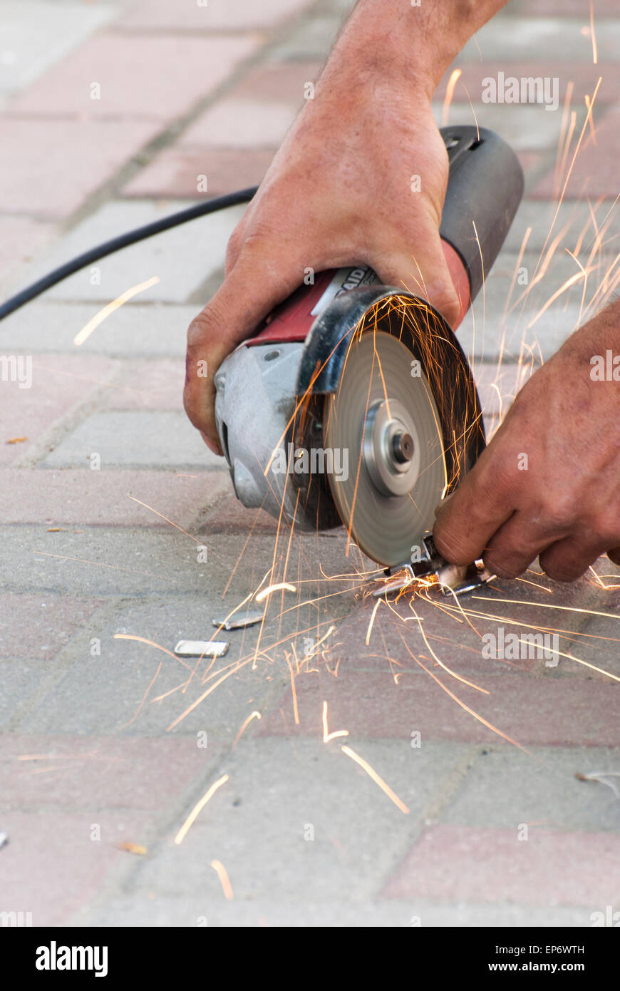 A man working by angle grinder - Stock Image