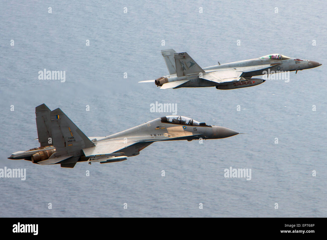 A U.S. Navy F/A-18C Hornet fighter aircraft flies in formation with a Russian made Royal Malaysian Air Force SU - Stock Image