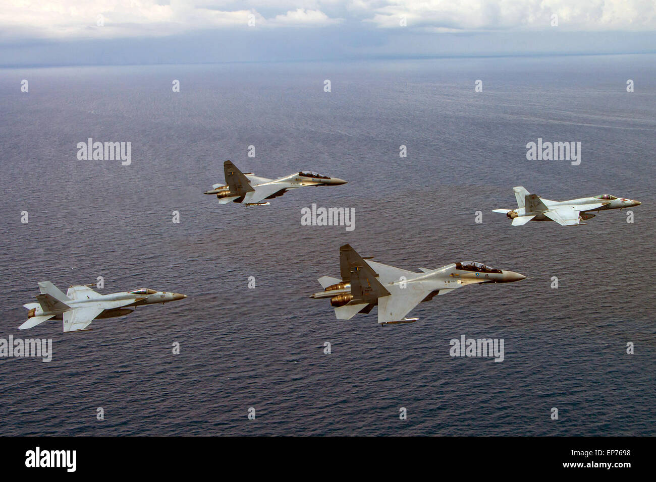 Two U.S. Navy F/A-18C Hornet fighter aircraft fly in formation with two Russian made Royal Malaysian Air Force SU - Stock Image
