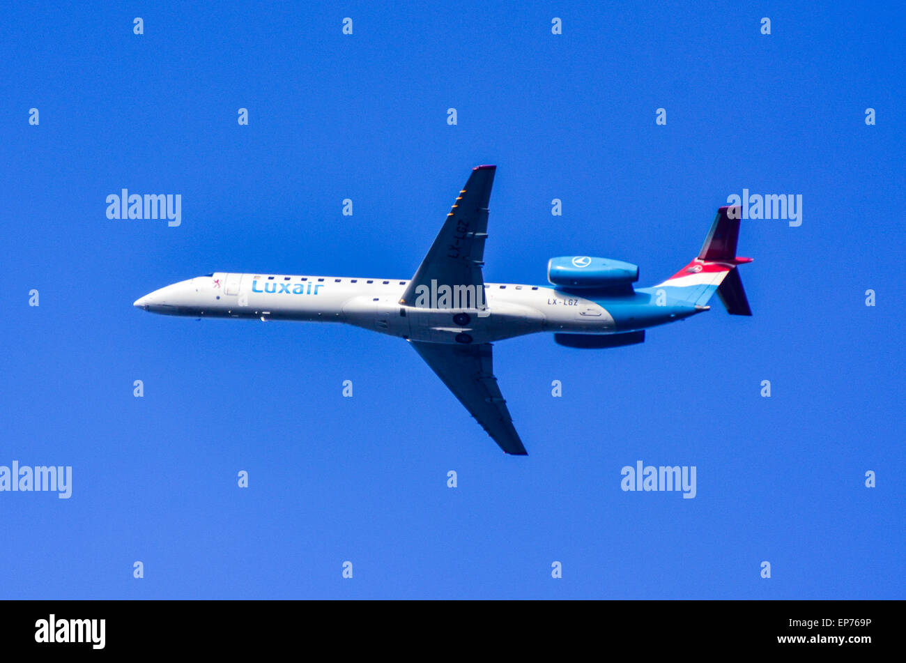 Luxair Embraer ERJ-145LU flying in the blue sky of Luxembourg - Stock Image