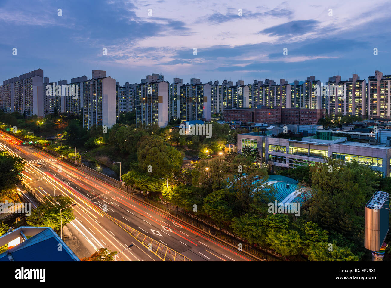 The sun sets over the endless apartment buildings among the suburbs of Seoul, South Korea. - Stock Image