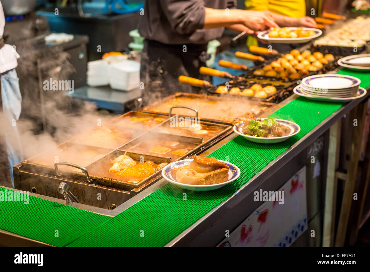 Ramen and oden put out on plates at a street food stall in Osaka, Japan. - Stock Image
