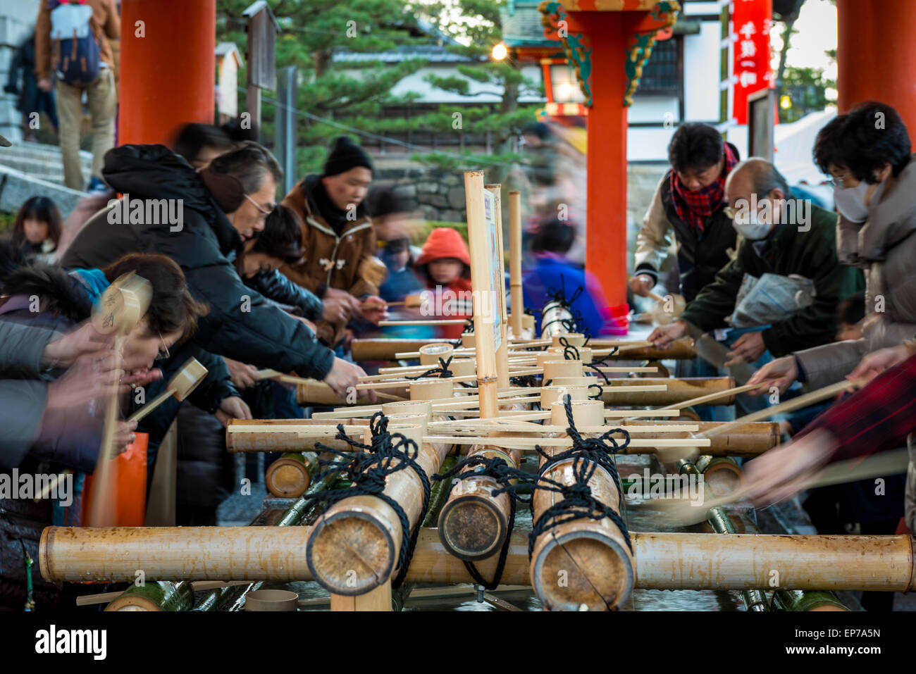 Japanese people purify their hands and mouths with water before entering Fushimi Inari Shrine on New Year's - Stock Image