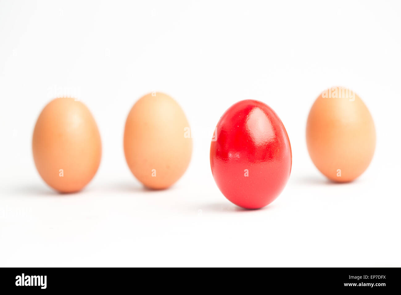 Four eggs in a row with one red one standing out - Stock Image