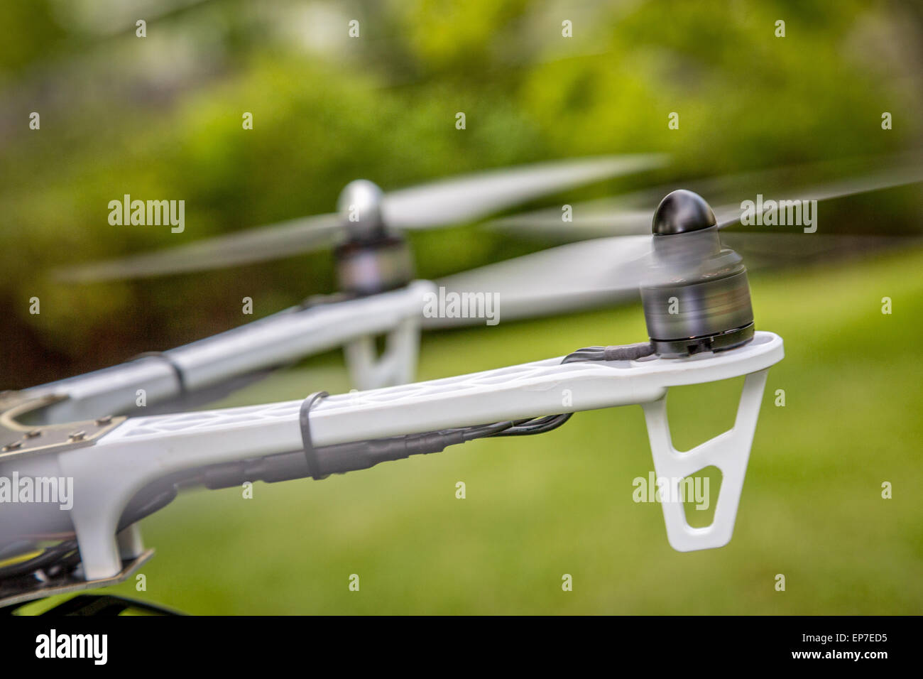 blurred spinning propellers of a hexacopter drone flying over green area - Stock Image