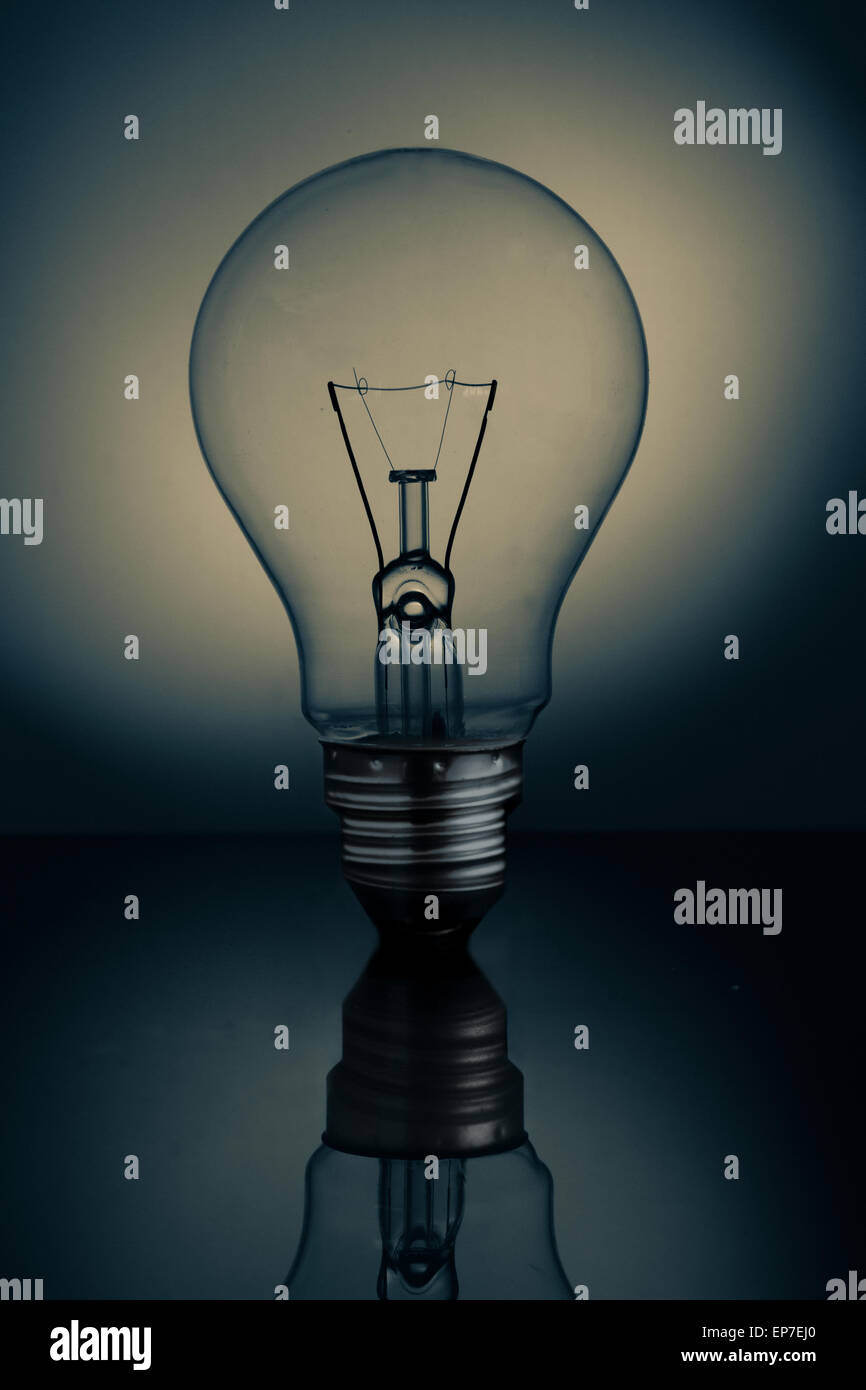 Big clear light bulb standing on reflective surface - Stock Image