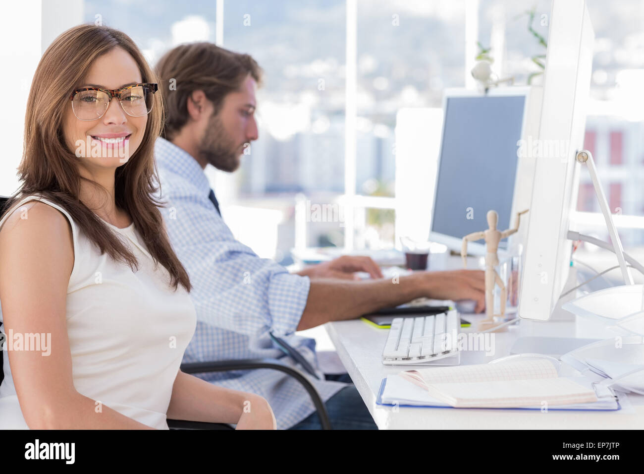 Portrait of smiling designer with reading glasses - Stock Image