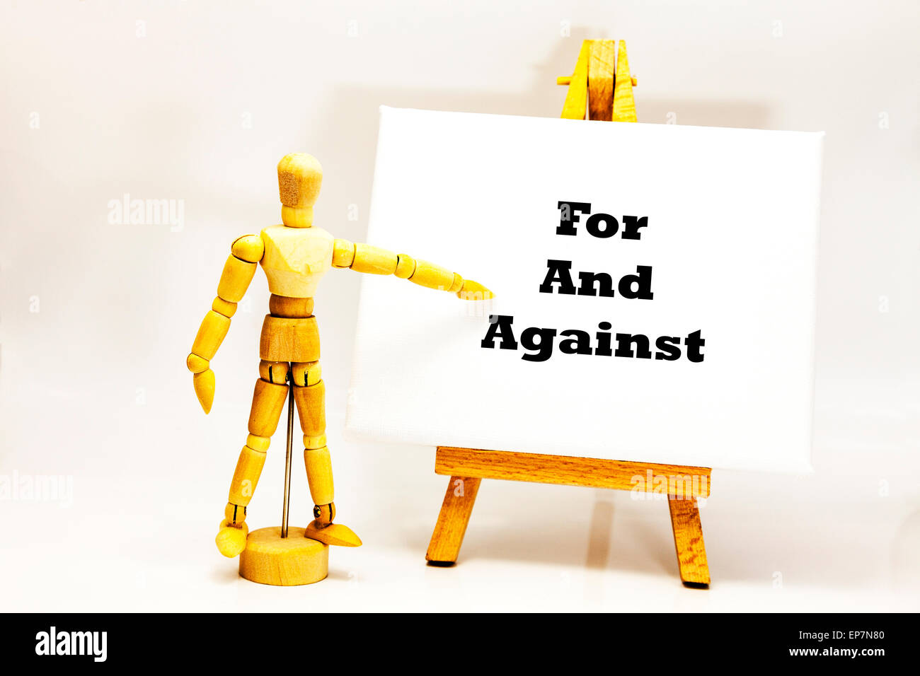 Wooden man with white board pointing at words 'For And Against' pros and cons choice choose choices Yes - Stock Image