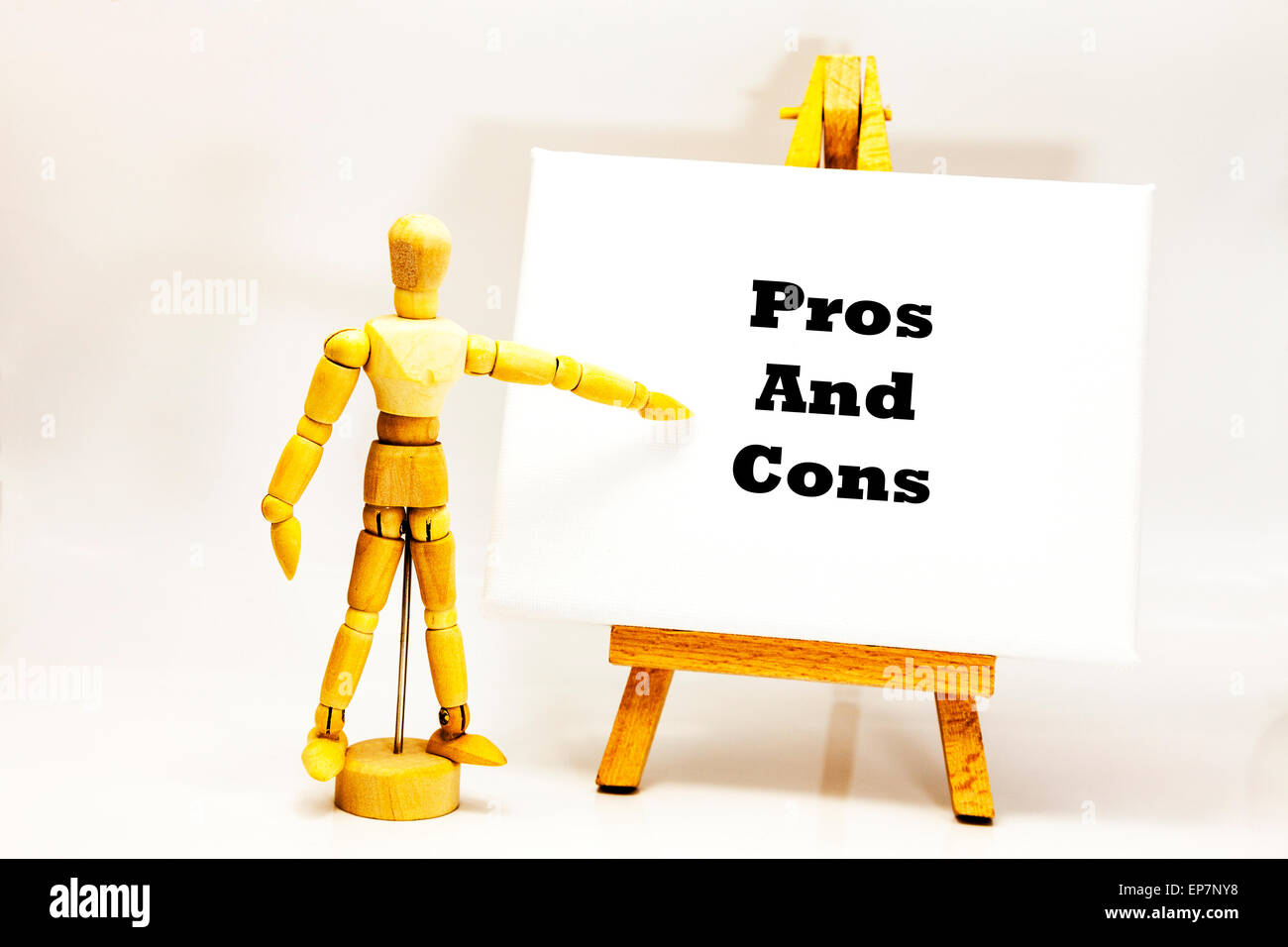 Wooden man with white board pointing at words 'Pros And Cons' for against list behalf of contrā contra The - Stock Image