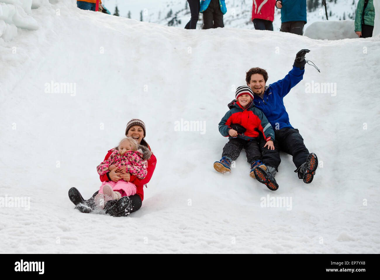 Laughing family slides down snow slide with his young daughter at Squaw Valley Ski Resort in California - Stock Image