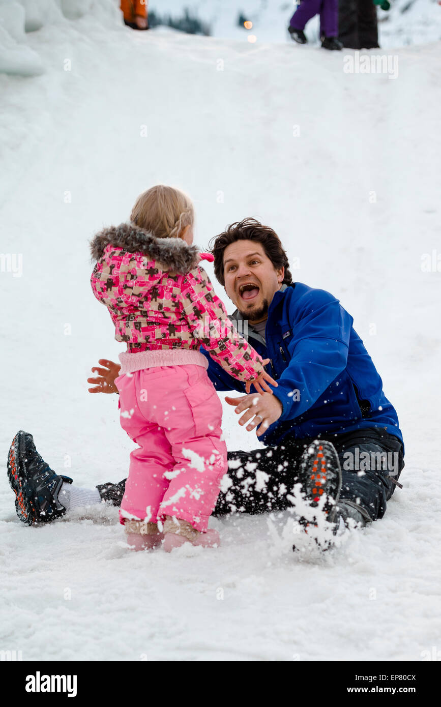 Laughing father slides down snow slide with his young daughter at Squaw Valley Ski Resort in California - Stock Image